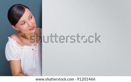 Closeup of young, pretty woman standing near huge blank board and holding it. Lots of copyspace for your text and logo - stock photo