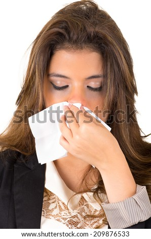 Closeup of young pretty working woman blowing her nose with a tissue isolated on white