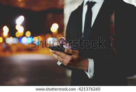 Closeup of young professional businessman wearing modern black suit and using smartphone outdoors at night city, bokeh light - stock photo