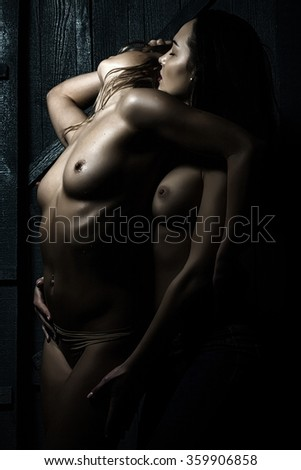 Closeup of young sexy female naked couple of two lesbian touching and embracing each other having sex with straight beautiful body undressed breast and nipples standing close indoor, vertical photo - stock photo