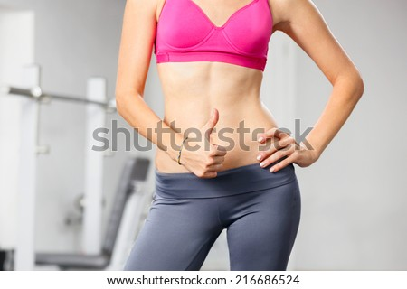 Closeup of young slim woman with six-pack torso. - stock photo