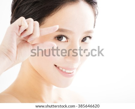 Closeup of young smiling woman eyes with gesture - stock photo