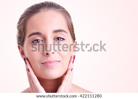 Closeup of young woman face isolated on pink background - stock photo