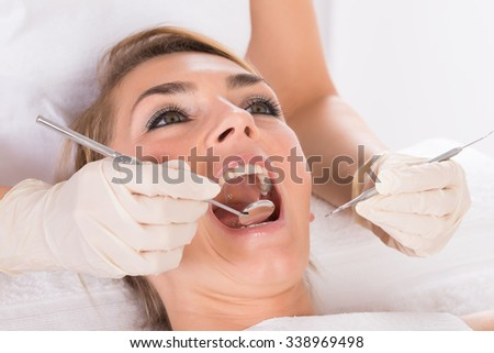 Closeup of young woman getting checkup at dentist's office - stock photo
