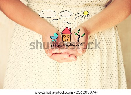 closeup of young woman hands. hands outstretched in cupped shape.sketches of house tree and birds as imagination or future dreams. selective focus. retro toned image.  - stock photo