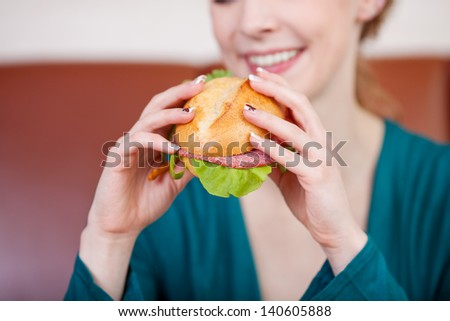 Closeup of young woman holding burger in coffeeshop - stock photo