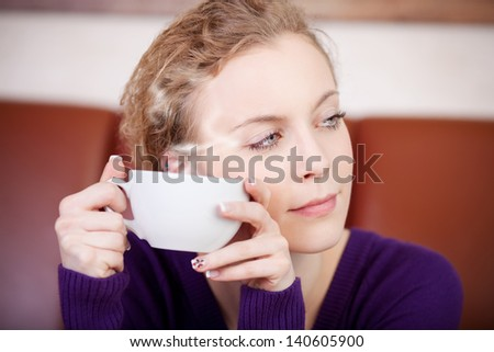 Closeup of young woman holding coffee cup while looking away in cafe - stock photo