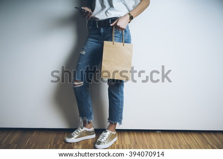 Closeup of young woman in blue jeans using smart phone and holding blank craft package, mock-up of brown paper bag with handles - stock photo