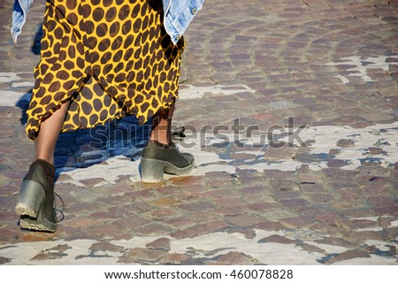 Closeup of young woman legs on crossing Parisian cobblestone street.