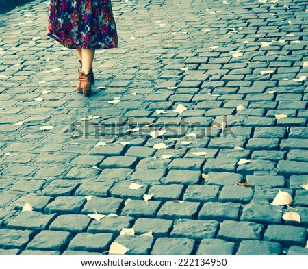 Closeup of young woman legs on Parisian cobblestone street covered with yellow autumn leaves. Retro aged photo. - stock photo