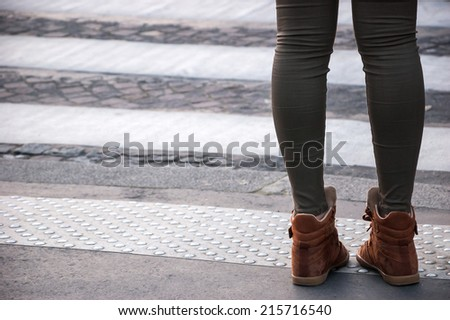 Closeup of young woman legs waiting at crosswalk. - stock photo