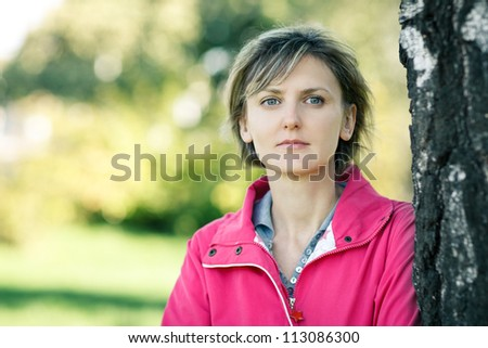 Closeup of young woman outdoors in fall clothing with autumn natural surroundings leaning on the tree stem, with copy space - stock photo