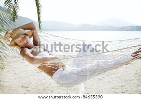 closeup of young woman relaxing in a hammock by the beach - stock photo