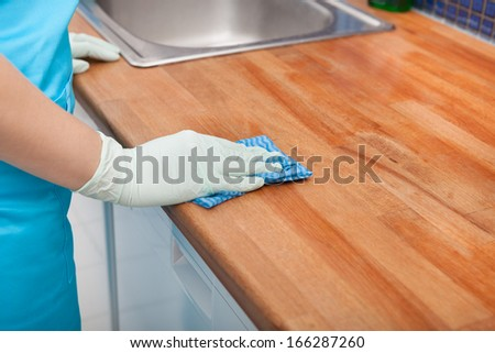 Closeup Of Young Woman Wearing Apron Cleaning Kitchen Worktop - stock photo