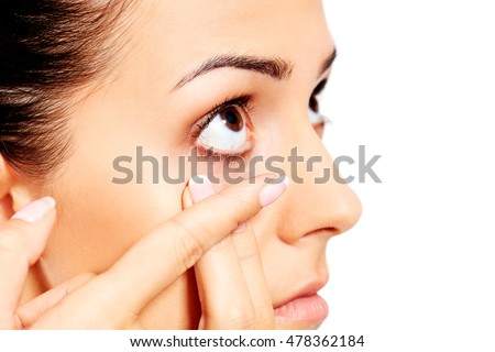 Closeup of young woman wearing contact lens.