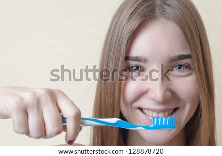 Closeup of young woman with a tooth brush on her hands about to brush her teeth on beige background