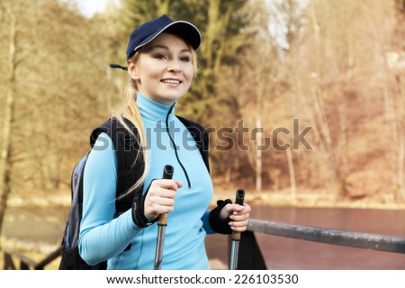 Closeup of young woman with Nordic walking poles in spring village  - stock photo