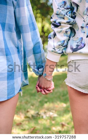 Closeup of young women friends with shorts holding hands over a nature background.