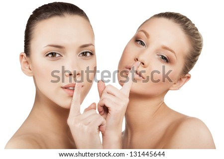closeup of young women making a hush gesture, isolated - stock photo