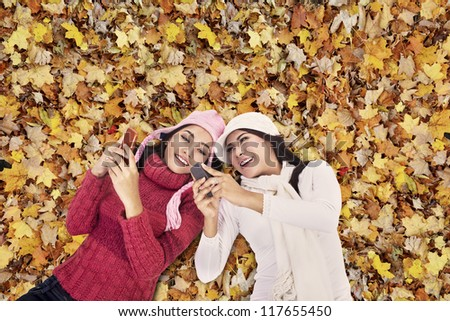 Closeup of young women wearing winter clothes playing mobile phone over autumn foliage - stock photo