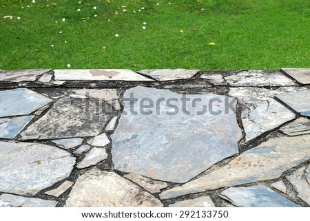 closeup old and dirty stone floor with blur grass background - stock photo