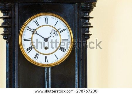 Closeup old big wooden pendulum clock hanging on wall