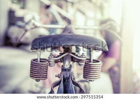 Closeup old bike saddle with rusty metal spring in vintage color tone - stock photo