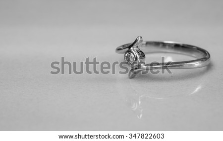Closeup old diamond ring on blurred marble floor background in black and white tone