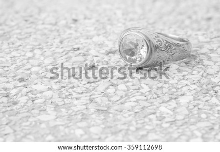 Closeup old diamond ring on blurred stone floor background in black and white tone - stock photo