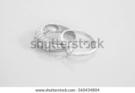 Closeup old diamond rings on blurred marble stone floor background in black and white tone - stock photo