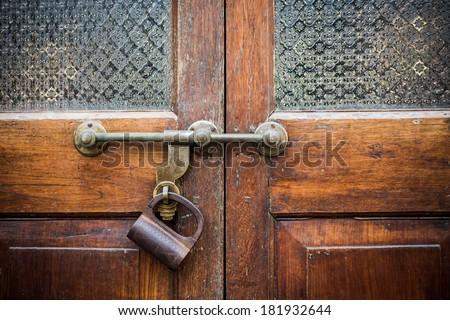 Closeup old door with lock in grungy style and wood texture. - stock photo
