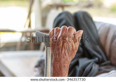 Closeup old hand with crutch - stock photo