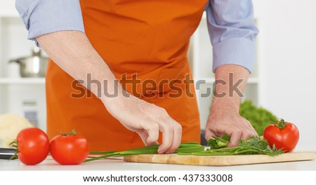 Closeup old man's hands cutting onions on a work surface in a kitchen. - stock photo