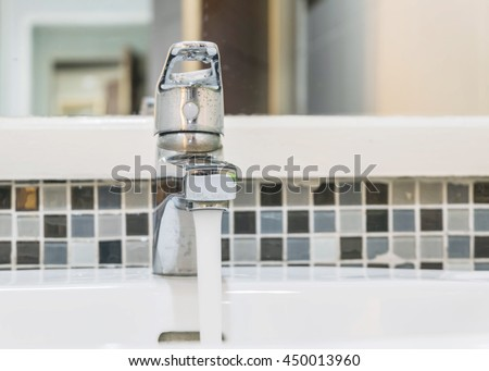 Closeup old open stainless faucet in the toilet with interior of toilet view background - stock photo