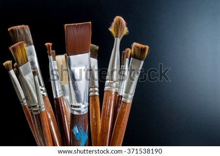 Closeup old paint brushes on black background with light side view.