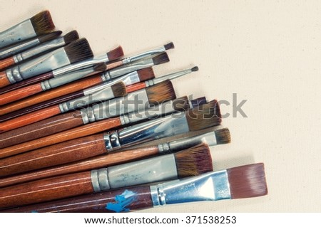 Closeup old paint brushes on canvas fabric background.