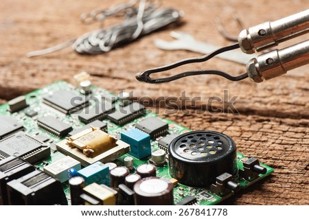 closeup old soldering iron isolated on wooden desk  - stock photo