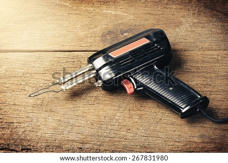 closeup old soldering iron on wooden desk - stock photo