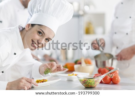 closeup on a  female chef preparing a dish her team in the background - stock photo