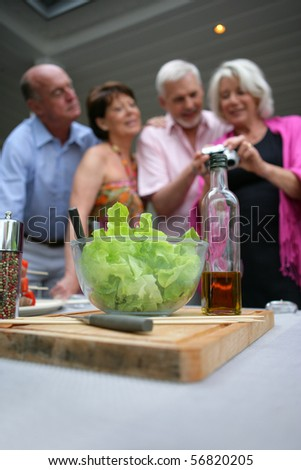 Closeup on a green salad on a table near a senior group watching a digital camera - stock photo