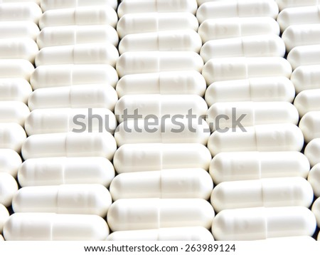 Closeup on a lot of white tablets in a row.