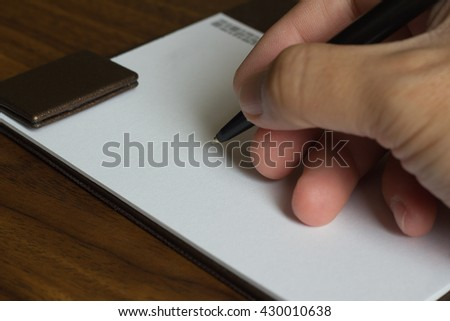 Closeup on a man's hand writing on white blank paper note with a pen