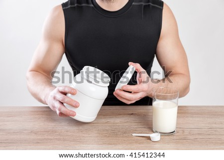 Closeup on a man with nutrition and protein supplements on table - stock photo