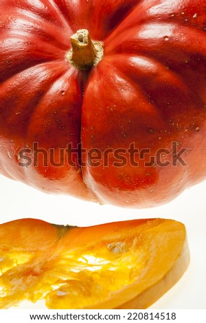 Closeup on a slice of orange pumpkin with pulp and seeds in the foreground.n. - stock photo