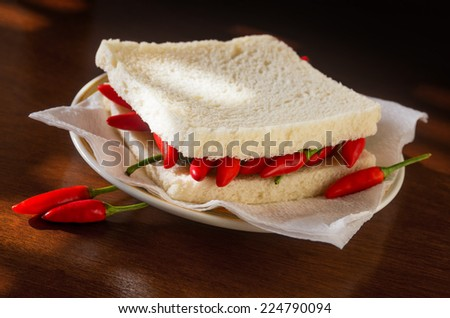 Closeup on a spicy hot chili pepper sandwich in a plate - stock photo