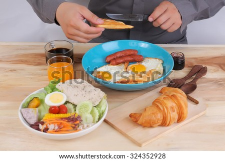 Closeup on a young man's hands as he is having breakfast
