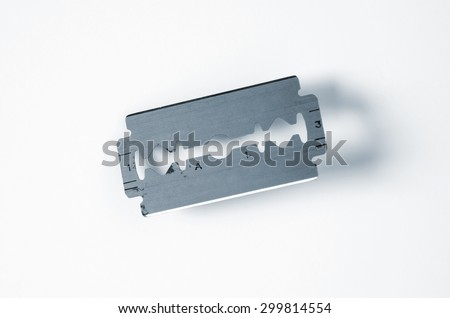 Closeup on an old razor blade over a white background - stock photo
