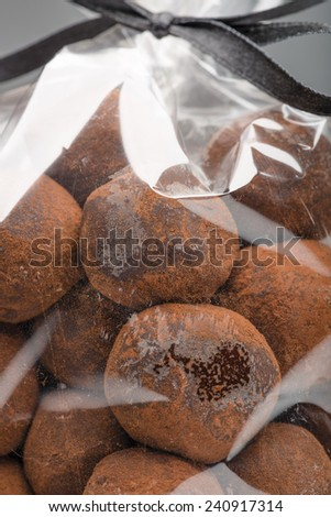 Closeup on appetizing chocolate truffles bag with elegant black ribbon in background. Shooting in studio on grey background. - stock photo