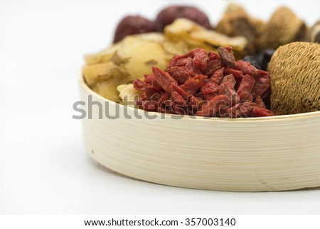 Closeup on assortment of Chinese herbal soup ingredients in a bamboo bowl focusing on the red wolfberries at foreground, blurring out other ingredients.  Isolated on white background. - stock photo
