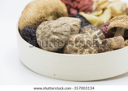Closeup on assortment of Chinese herbal soup ingredients in a bamboo bowl focusing on the shiitake mushroom at foreground, blurring out other ingredients.  Isolated on white background. - stock photo